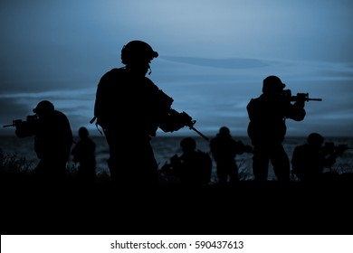 Silhouette of soldiers with rifle on a sunset dark background. War, military and danger concept.