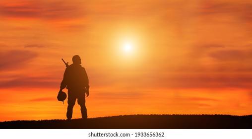 Silhouette Of A Solider Saluting Against the Sunrise. Concept - protection, patriotism, honor.