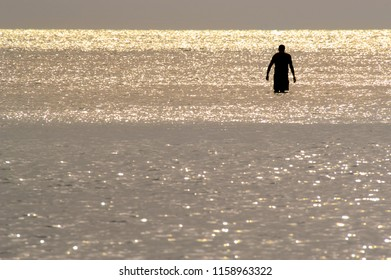 Silhouette of a solitary man wading in shiny water at sunset on Barefoot Beach, Florida.