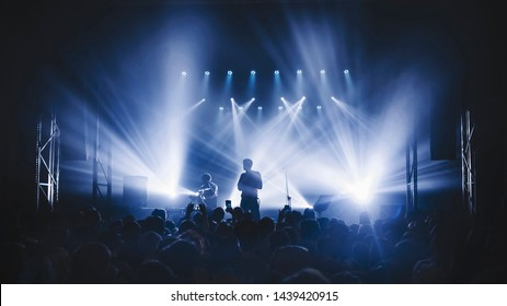 silhouette of the soloist standinf in a fog in the rays of light. concert crowd in front of bright stage lights. Dark background, smoke, concert  spotlights