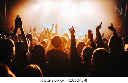 silhouette of the soloist / vocalist stands in a fog in the rays of light. concert crowd in front of bright stage lights. Dark background, smoke, concert  spotlights