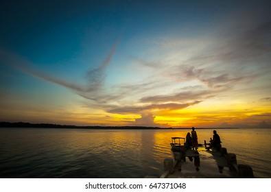 Silhouette of some people enjoying beautiful beach at dawn in Hoga Island, Wakatobi, Indonesia