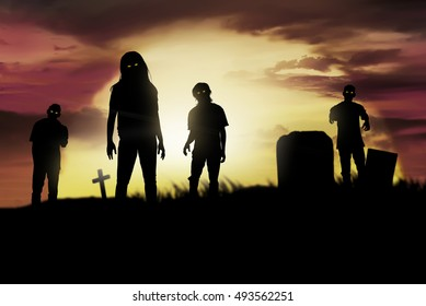 Silhouette some zombies on the cemetery walking around at sunset