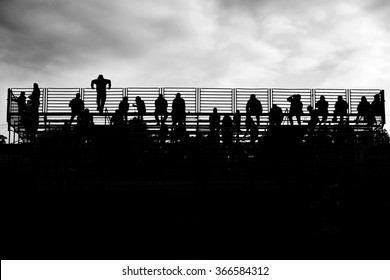 Silhouette of spectators watching a drag race.