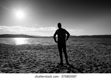 Silhouette of sport active adult man running and exercising on the beach. Calm water, island and sunset sky background. Black and white photo.