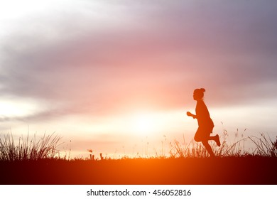 Silhouette of sport active women running and exercising on the sunset.