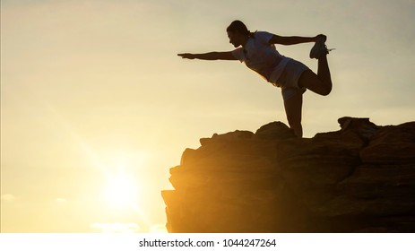 Silhouette sport beautiful woman perform yoga exercise on top of hill during sunset after climbing to mountain summit peak with copy space for text. Success to goal. Business and Health concept.