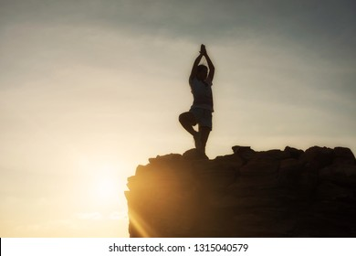 Silhouette sport beautiful woman stand on hill summit to perform yoga exercise  during sunset after climbing to mountain peak with copy space for text. Success to goal. Business and Health concept.