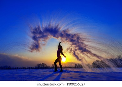 Silhouette of a sports girl at sunset in winter. Woman splashed boiling water on cold air.