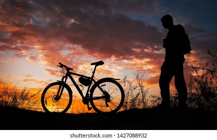 Silhouette of sports person cycling on the meadow on the beautiful sunset. Young man with camera and bicycle.