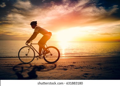 Silhouette of sportsman riding a bicycle on the beach. Colorful sunset cloudy sky in background.