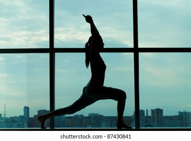 Silhouette of sporty girl doing physical exercise