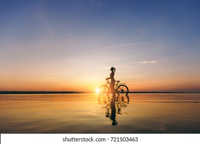 The silhouette of a sporty girl in a suit that sits on a bicycle in the water at sunset on a warm summer day. Fitness concept. Sky background