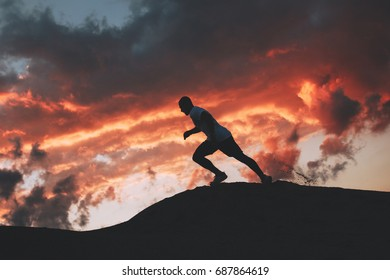 Silhouette of a sporty man running down the hills. Running at sunset