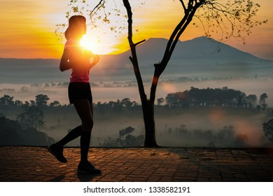 silhouette sporty woman jogging at park in sunrise