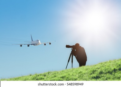 Silhouette of spotter photographer with camera and telephoto lens capturing photos of landing airliner. Aircraft or plane spotting is a hobby of tracking airplanes which accomplished by photography.
