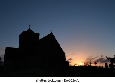 The silhouette of St Martha's on the Hill in Surrey at dawn.  Clear blue sky with some clouds where the sun is.