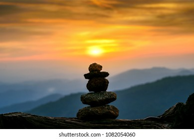 silhouette stack zen stones in sunset   with landscape mountains background, concept of balance and harmony