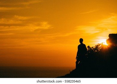 A silhouette stand by the sea on the edge of the cliff and looking at sun valley. Man enjoying a sunset or sunrise from top of the mountain in summer. Traveler see the sunrise at the peak of mountain.