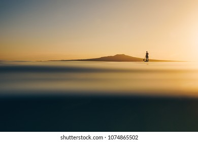 Silhouette of stand up paddle boarder paddling at sunrise in New Zealand