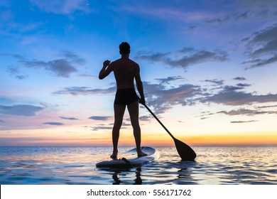 Silhouette of stand up paddle boarder paddling at sunset on a flat warm quiet sea