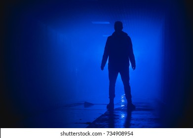 Silhouette standing man in the darkness. Blue background.