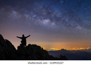 silhouette of a standing man on top of a cliff with arms raised at night landscape mountain and milky way  galaxy background , Thailand , long exposure ,low light