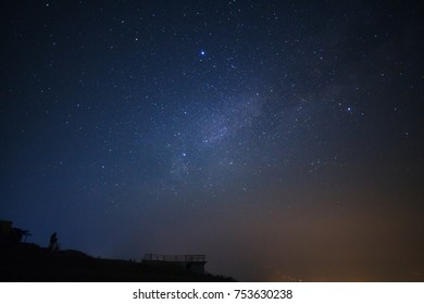 Silhouette of a standing man with telescope or camera watching the wilky way galaxy