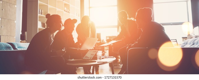 Silhouette of startup business team. Meeting on the couch. Big open space office. Five people. Intentional sun glare and lens flares. Wide screen, panoramic