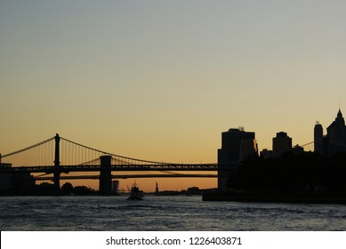 Silhouette of the Statue of Liberty and the Brooklyn Bridge at sunset.