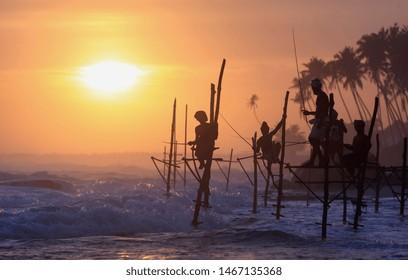 Silhouette stilt fishermen fishing in sunset beach