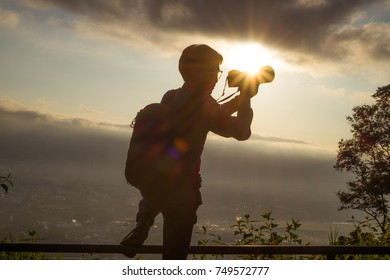 silhouette of Stock Photo contributors tourism explore forests in Asia. hand holding camera holding pro digital camera with telephoto lens. Photo Stock career. Stock Photo contributors Concept