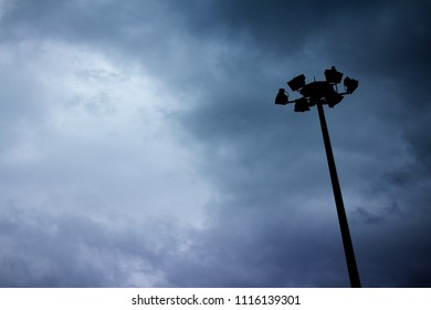Silhouette street flood light pole with dark stormy cloudy sky and partial circle opening in the background. With room for text and copy space. Blackout or energy crisis concept.