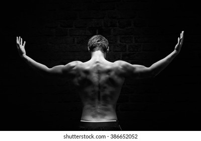 Silhouette of a strong, athletic man with dramatic light and dark background
