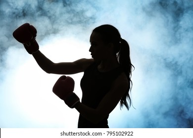Silhouette of strong boxer woman on dark background