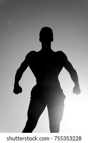 Silhouette of strong man. Sportsman relaxing muscles, biceps, triceps. Fitness and sport concept. Bodybuilder posing on sky and sun light. Athlete showing muscular body in dusk, black and white