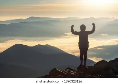 Silhouette of strong woman on mountain peak flexing her muscle demonstrating self-confidence and courage.