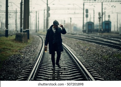 silhouette of stylish gangster man with bottle whiskey walking on railway road. england in 1920s theme. fashionable brutal confident man. atmospheric moments
