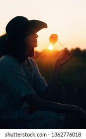 Silhouette of stylish girl in linen dress holding poppy flower in meadow in sun light with flowers in rustic straw basket. Boho woman in hat relaxing in summer sunset field. Atmospheric