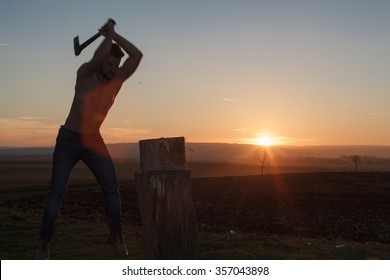 Silhouette stylish lumberjack chopping wood at sunset (Motion blur hands and axe).