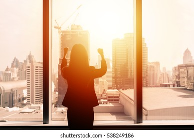 Silhouette of success businesswoman with arms up by office window with cityscape in background with sunlight.