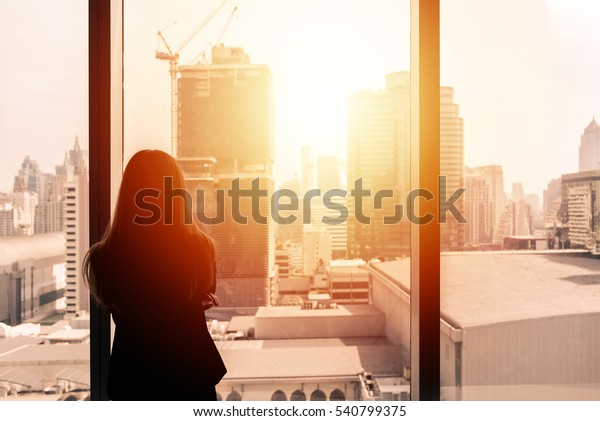 Silhouette of success businesswoman thinking by office window with cityscape in background with sunlight.
