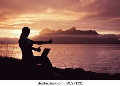 Silhouette of a successful slender girl, using laptop, sitting on top of a mountain, outdoor. Sunset in the mountains Ocean fjord views. Vacation, freelance, working outdoor, communication in internet