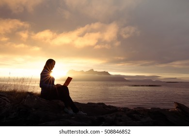 Silhouette of a successful slender girl, using laptop, sitting on top of a mountain, outdoor. Sunset in the mountains Ocean fjord views. Vacation day, freelance, working, communication in internet