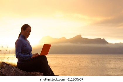 Silhouette of a successful slender girl, using laptop, sitting on top of a mountain, outdoor. Sunset in the mountains Ocean fjord views. Vacation day, freelance, working outdoor, communication