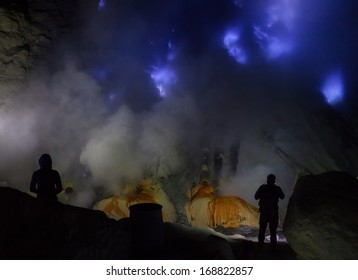 Silhouette of sulfur worker looking into the blue fire a flow of liquid sulfur which has caught fire and burns with an blue flame. Cater of the Kawah Ijen volcano, Java, Indonesia.