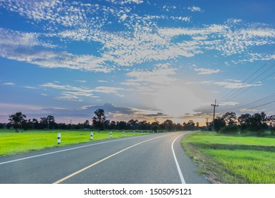 Silhouette the sunrise with the road, green paddy rice field, the beautiful sky and cloud in Thailand, by the beam, light and lens flare effect tone.
