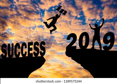 Silhouette sunset background. A man is jumping over to cliff and jump  across between start! and 2019 word.This photo shows about freedom,Active and successful,Photo Silhouette and new year.