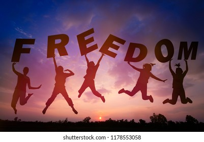 Silhouette sunset background and Team work .They are jumping in to sky and lift  freedom word. They are happy and fun, activity , out door, Photo Silhouette and success  concept idea.