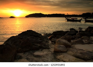 Silhouette sunset seascape of natural stone arch on beach and wooden boats on Andaman sea at Koh Lipe, Satun, Thailand.